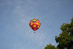 Colorful Hot Air Balloon flying overhead at Ashland Balloonfest. Colorful striped hot air balloon flying overhead at the Ashland Balloonfest in Ashland, Ohio stock photo