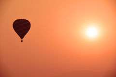 Colorful hot air balloon is flying at sunset Stock Photos