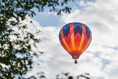 Colorful hot air balloon framed by leaves. A hot air balloon ascending into a blue sky with light cloud cover. Leaves on the side of the frame royalty free stock photo