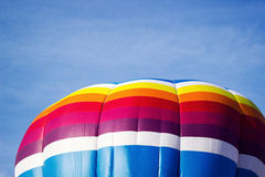 Colorful hot air balloon moving up in blue sky. Stock Photos