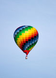 Colorful hot air balloon moving up in blue sky. Stock Photo