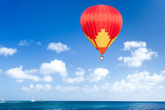 Colorful hot air balloon. Over blue sea Stock Image