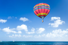 Colorful hot air balloon. Over blue sea Royalty Free Stock Images