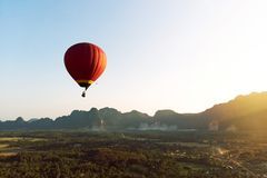 Colorful hot-air balloon raising just in time to explore beautiful sunset over Vang Vieng in Laos, Southeast Asia. Red hot-air balloon raising just in time to stock photos