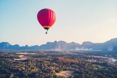 Colorful hot-air balloon raising just in time to explore beautiful sunset over Vang Vieng in Laos, Southeast Asia. Red hot-air balloon raising just in time to stock image