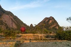 Colorful hot-air balloon raising just in time to explore beautiful sunset over Vang Vieng in Laos, Southeast Asia stock photo
