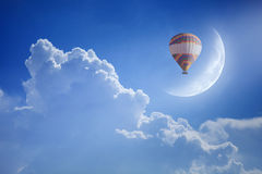 Colorful Hot Air Balloon Rise Up Into Blue Sky Above White Cloud Stock Photo
