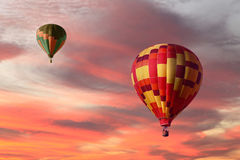 Colorful Hot Air Balloons Ascending in a Sunrise. Colorful Hot Air Balloons Ascending in a Orange Sunrise Stock Photos
