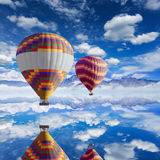 Colorful hot air balloons flies above calm lake Royalty Free Stock Photo