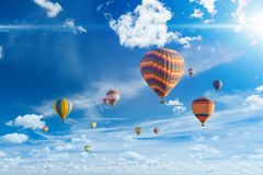 Colorful hot air balloons fly in blue sky with white clouds stock photos