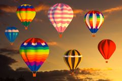 Colorful hot air balloons fly in the sunset sky Royalty Free Stock Photos