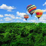Colorful hot air balloons flying high. Hot air balloons over the forest with blue sky Royalty Free Stock Photography