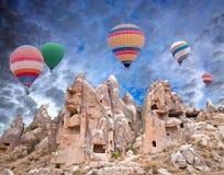 Colorful hot air balloons flying over Cappadocia, Anatolia, Turk. Panorama of unique geological formations and colorful hot air balloons flying over Cappadocia Stock Image