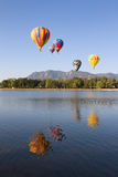 Colorful Hot Air Balloons flying over a lake. Multi color hot air balloons flying over a lake with the mountains in the background. Their reflections are in royalty free stock image
