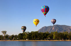 Colorful Hot Air Balloons flying over lake. Multi color hot air balloons flying over a lake with the mountains in the background. Their reflections are in stock images