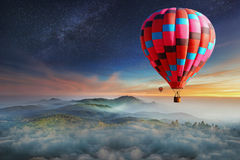 Colorful hot-air balloons flying over the mountain with with sta. Rs. Beautiful mountains landscape with clouds at sunset Royalty Free Stock Photo