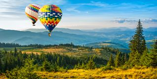 Colorful hot-air balloons flying over the mountains. Artistic pi royalty free stock photography