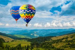Colorful hot-air balloons flying over the mountains. Artistic pi stock images