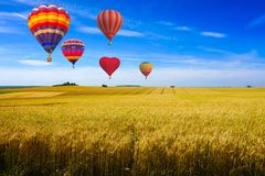 Colorful hot air balloons flying over reaped field and green hill view on a sunny day at sunset montagne de Reims. France Stock Photo