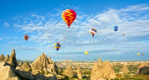 Colorful hot air balloons flying over volcanic cliffs at Cappadocia, Anatolia, Turkey. Panorama stock photo