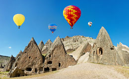 Colorful hot air balloons flying over volcanic cliffs at Cappadocia stock images