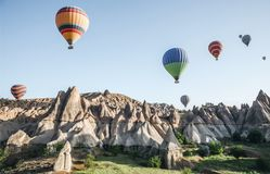 colorful hot air balloons flying in sky above beautiful rock formations in cappadocia, turkey В  stock images