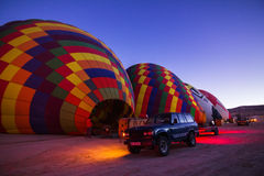 Colorful hot air balloons inflating before the flight at sunrise. GOREME - OCTOBER 10: Colorful hot air balloons inflating before the flight at sunrise with car Royalty Free Stock Photo