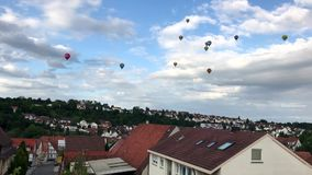 Colorful hot air balloons over village stock video