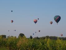 Hot air balloons racing across horizon. Colorful hot air balloons racing high in the blue sky across a farm field Stock Image