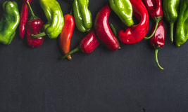 Colorful hot chili peppers on black wooden background, copy space Royalty Free Stock Photography