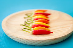 Colorful hot chili peppers in a row on plate Stock Photo