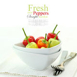 Colorful hot mini chili peppers in white bowl stock photography