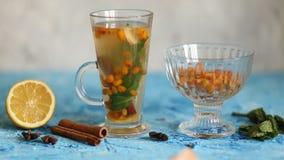 Colorful hot sea buckthorn tea with cinnamon sticks, star anise and fresh sea buckthorn berries stock video footage