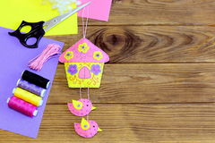 Colorful house with birds decoration, thread, scissors, felt sheets and scraps on the table. Beautiful house with birds Stock Photos