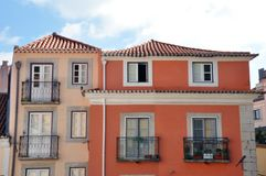 Houses in Lisboa, Portugal. Colorful house exteriors in Lisboa, Portugal against blue skies with clouds on sunny day Stock Photo