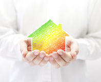 Colorful house in hands. Energy saving concept. Royalty Free Stock Photography