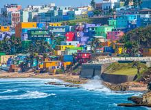Colorful house line the ocean front in San Juan, Puerto Rico. Ocean and wave don't Match the beauty of the colorful houses going up to Hillside in San stock photo