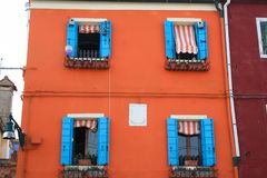 Burano. Colorful house in orange and blue  in the old town of Burano, a little island  in Venice lagoon, Italy Royalty Free Stock Photos