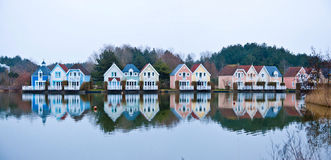 Colorful houses. Lake in front of colorful houses in France royalty free stock photography