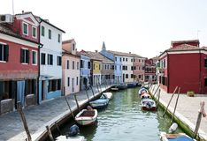 Colorful houses along a canal in Burano, Venice, Italy. Burano is an island in Venetian Lagoon known for its colored homes. Stock Photos
