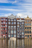 Colorful houses and boat at the Damrak in Amsterdam Stock Photo