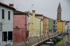 Colorful houses in Burano island near Venice, Italy on water canal with boats. royalty free stock photography