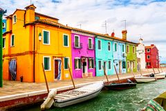 Colorful houses in Burano near Venice, Italy with boats and beautiful blue sky in summer. Famous tourist attraction in Venice.  stock photography