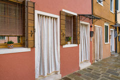 Colorful houses on Burano. Several doors and windows with typical curtains stock photos