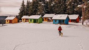 Colorful houses on a coast of a frozen lake. Mountain biker and Royalty Free Stock Photography