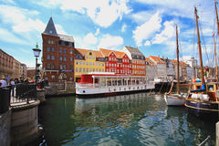 Colorful houses in Copenhagen old town with boats and ships in the canal in front of them Stock Images