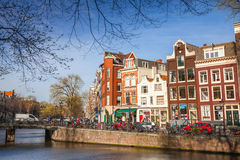 Colorful houses facades on canal in spring sunny day in Amsterdam Stock Images