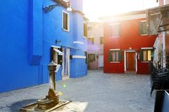 Colorful houses and a fountain in Burano, Venice, Italy Stock Photos