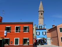 Colorful houses in front of the leaning tower of San Martino Church. stock image