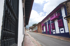 Colorful houses at La Candelaria in Bogotá. Perspective view of a street with colonial houses and balconys at the historical district know as La Candelaria in Royalty Free Stock Photography